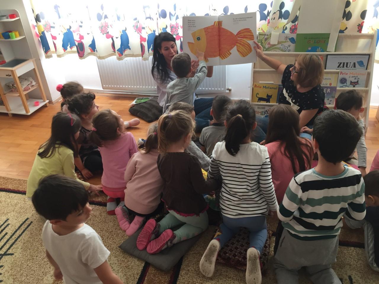 Volunteers reading to kindergarten children from marginalized areas of Bucharest